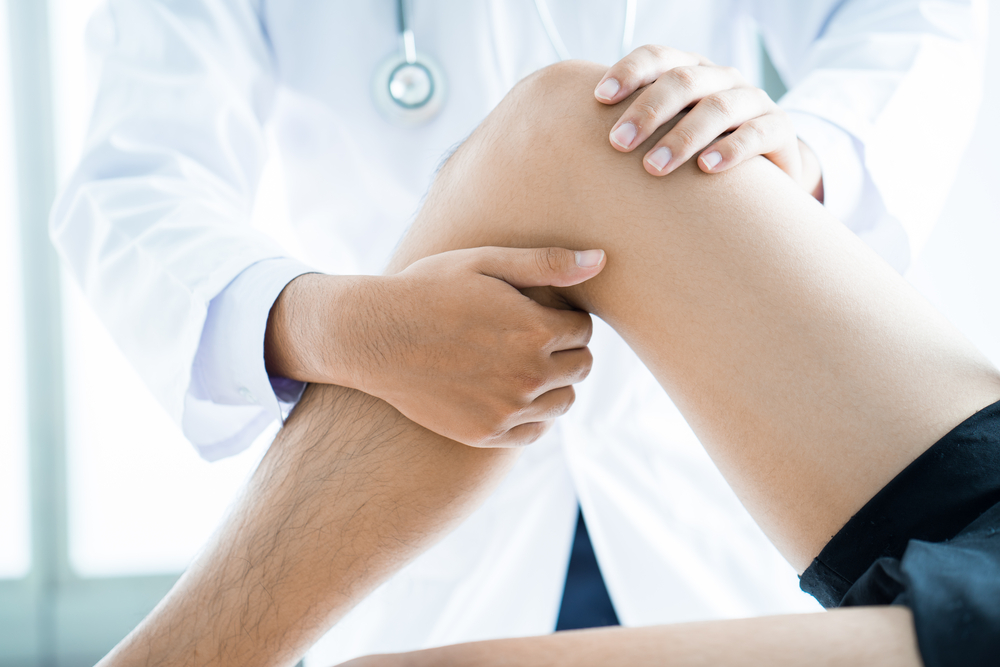 Doctor examining a patients leg during a sports/employment physical